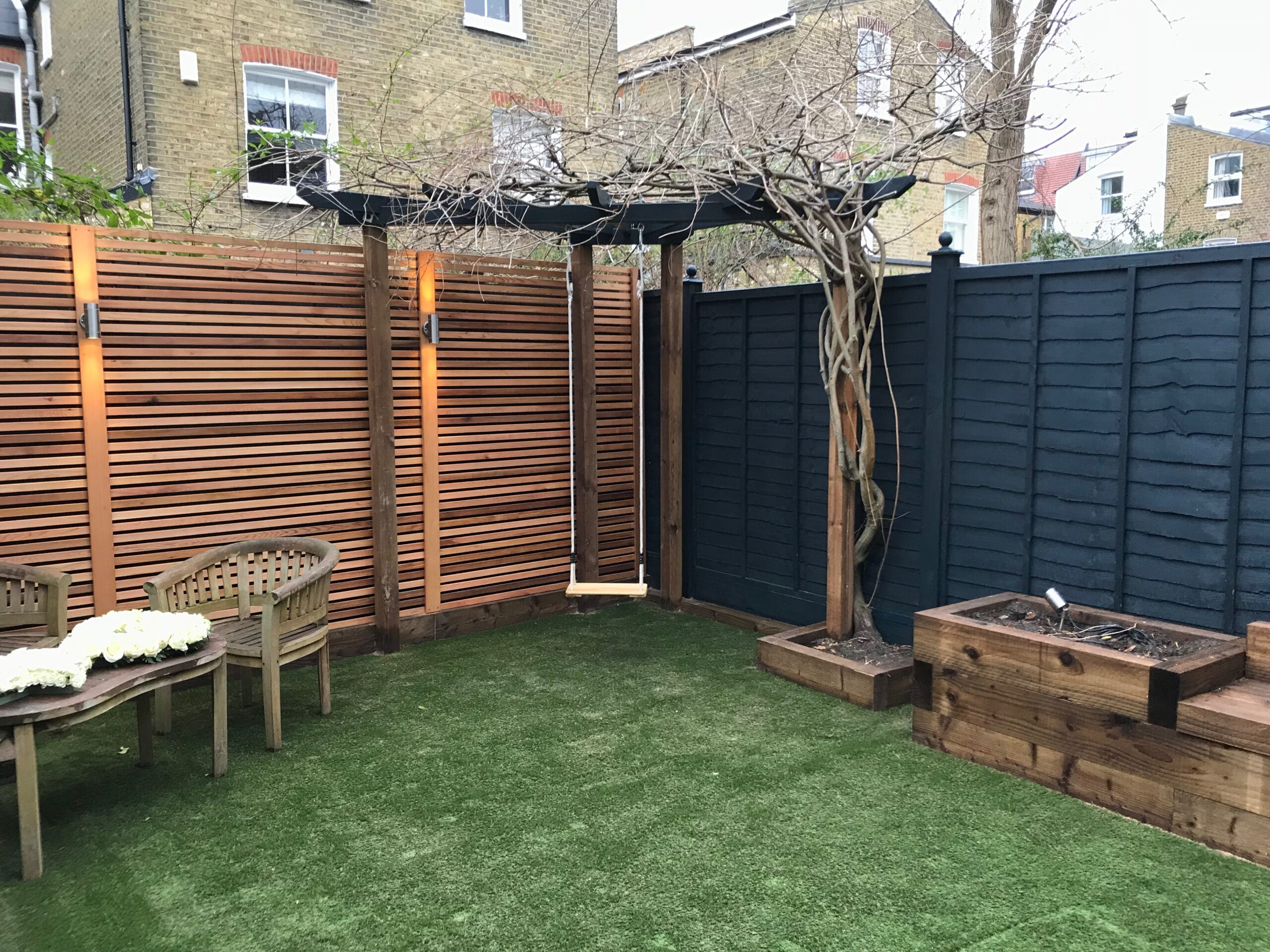 A neat garden transformation - including uplighting along fencing and a swing!